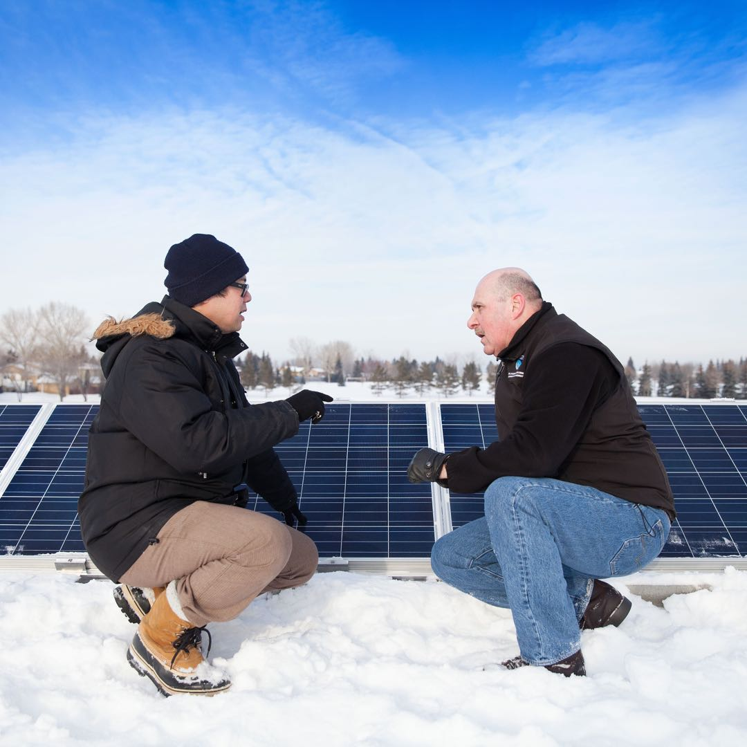 Two men talk about Community Solar Gardens in the snow. © NAIT 2016, made available under a Creative Commons 2.0 license.