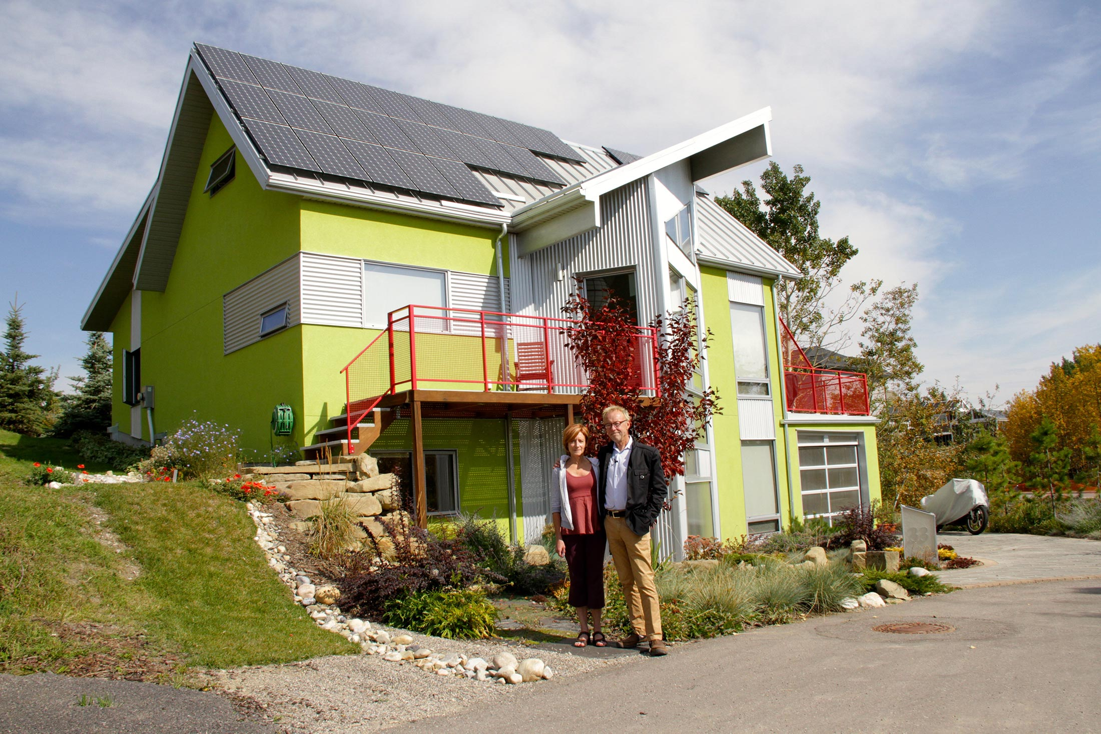 Homeowners stand in front of their solar powered home. © David Dodge, made available under a Creative Commons 2.0 license.